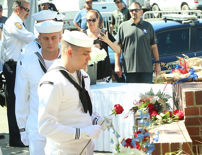 Sailors from Naval Air Station Fallon place roses at the city's 9/11 Memorial.