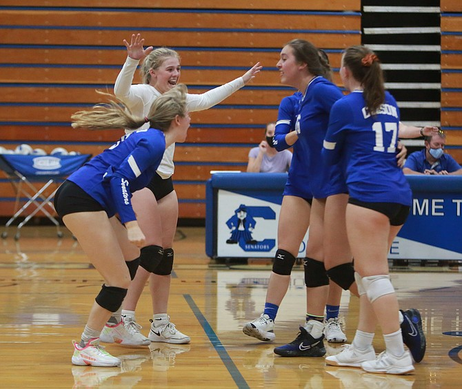 The Carson High volleyball team celebrates after winning match point against Reed at home Wednesday night.