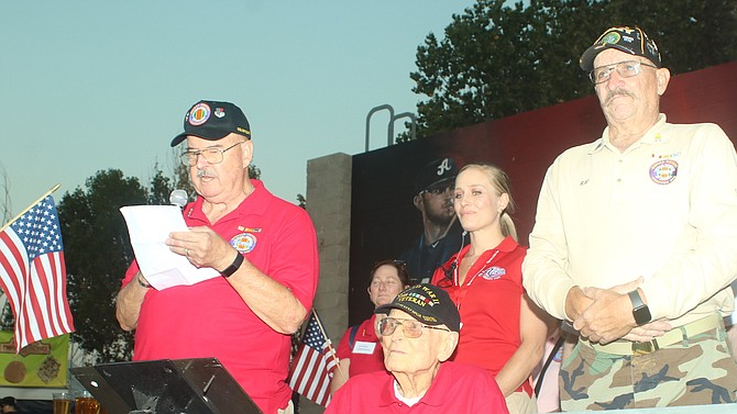 J.R. Stafford, left, president of the Vietnam Veterans of America, Sierra Nevada Chapter 989, reads information on the rededication of the POW/MIA seat at Greater Nevada Field. From Stafford's left are former POW John Leavitt, Aces General Manager Emily Jaenson and VVA member Ray Scow.