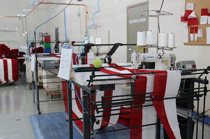 The striping machine at North Bay Industries stitches together long rows of red and white fabric, accounting for seven short stripes that sit beside the stars and the six long stripes lining the bottom of the American flag. (Photo: Faith Evans/Nevada Appeal)