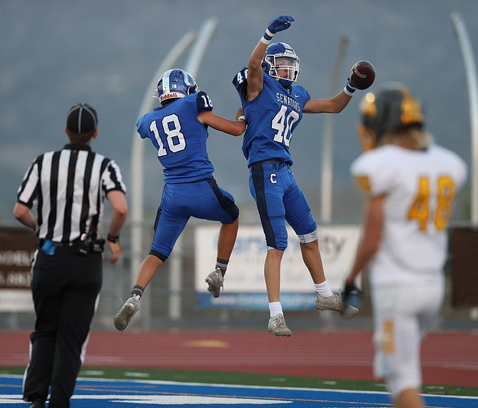 Carson High's Lucas Gonzales (18) and Mack Chambers (40) celebrate Chambers' 30-yard touchdown reception in the first quarter of the Senators' 48-0 shutout win over Galena.
