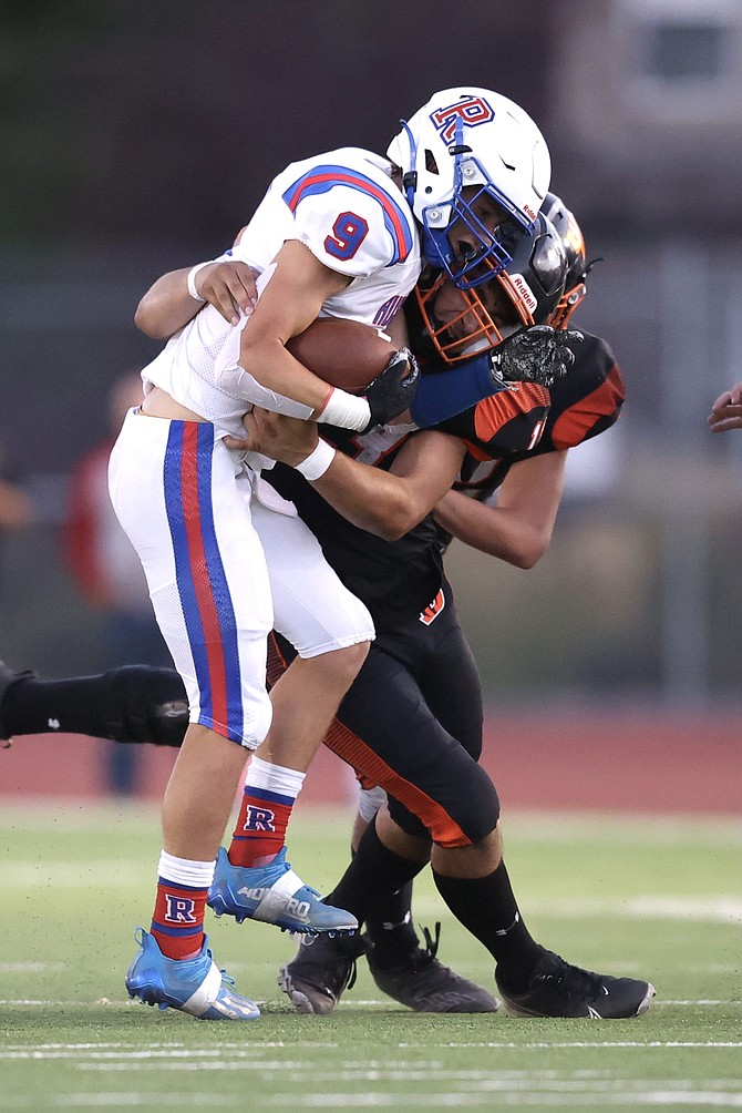 Douglas High linebacker Gabe Foster wraps up a Reno ballcarrier last Friday during the Tigers' home opener.