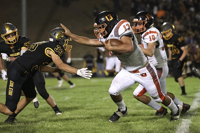 Douglas High running back Gabe Foster (13) stiff arms a Galena defender Friday evening. Foster ended the night with 226 rushing yards and four touchdowns.