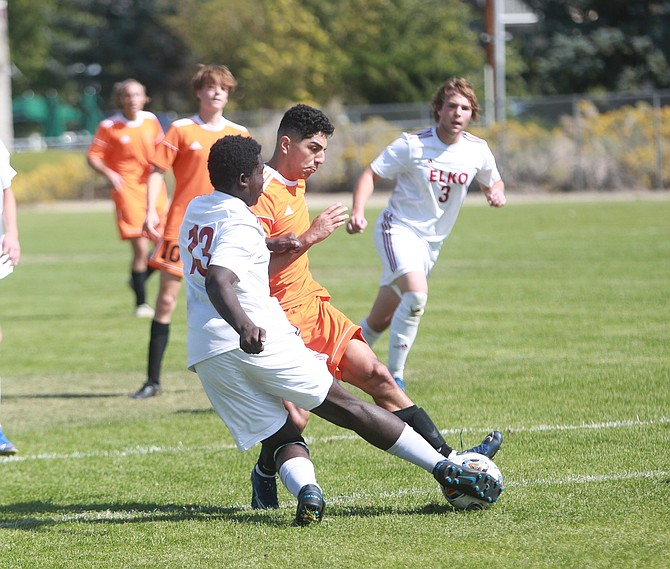 Douglas' David Jauregui-Fausto (11) attempts a shot in the box while Elko defender Jeremy Ankomah slides in to stop him.