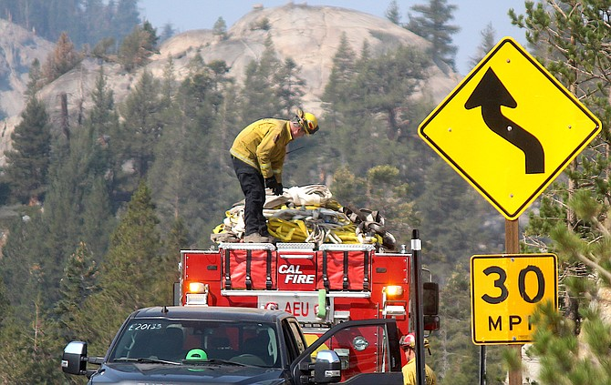 Firefighters roll up hose on Highway 88 on Thursday morning before Highway 88 opened. Expect to see fire, road and utility crews working along Highway 50 when it reopens on Tuesday.