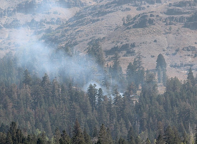 Smoke rises above Caples Lake on Sept. 16. Satellite mapping indicates the southern portion of the fire remains active.