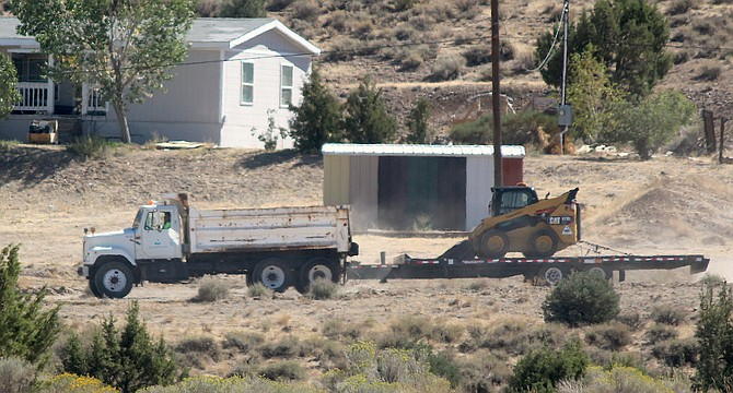 A Douglas County dump truck tows a bobcat on Courtland on Monday as law enforcement prepares to weed an alleged weed farm located over the ridge from Bodie Flat.