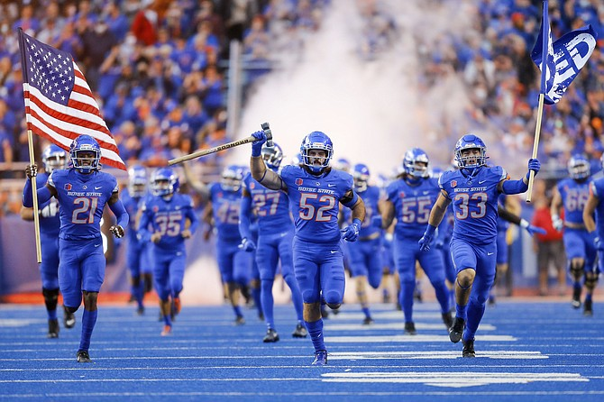 Boise State linebacker DJ Schramm (52), carrying the Dan Paul Hammer, running back Tyler Crowe (33), right, carrying the Bleed Blue flag, and Boise State safety Tyreque Jones (21), left, carrying the American flag, lead Boise State on to the field to face Oklahoma State on Sept. 18, 2021, in Boise, Idaho. Oklahoma State won 21-20. (AP Photo/Steve Conner)