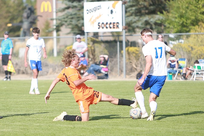 Douglas High's Bennjamin Peterson (23) slides in for a tackle on a McQueen ballhandler Thursday afternoon in the Tigers' 2-1 over the Lancers.