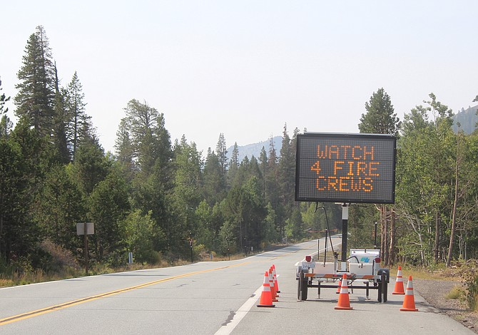 A sign warning motorists to watch for fire crews along Highway 88 just before Caples Lake. Firefighters are planning firing operations today to keep the Caldor Fire from burning any further east, weather permitting.