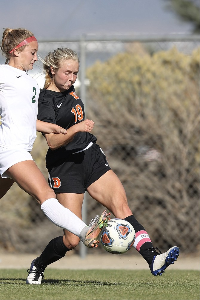 Douglas High's Bailey Rozier (19) works around Bishop Manogue's Reagan Stephens (2) during the Tigers' 1-1 draw with the Miners on Tuesday.