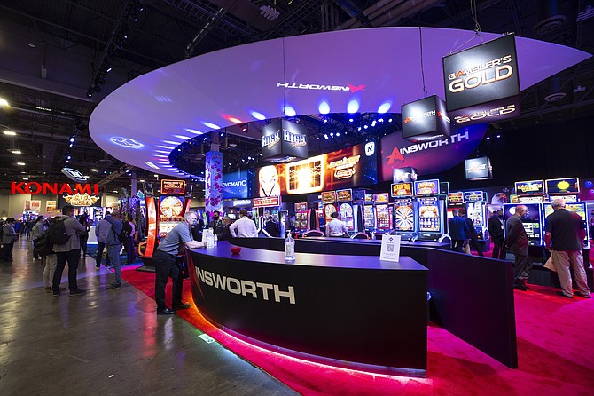 Attendees look over video slot machines at the Ainsworth Game Technology booth during the Global Gaming Expo (G2E) at the Venetian hotel-casino and Sands Expo Center in Las Vegas on Oct. 5, 2021. (Steve Marcus/Las Vegas Sun via AP)