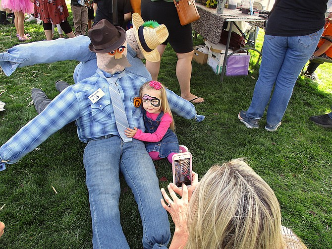 Little girl cuddles with a scarecrow during the scarecrow making event at the Fall Festival Saturday.