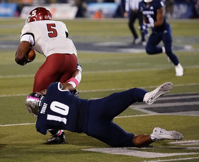 Nevada's Lamin Touray tackles NMSU's O'Maury Samuels.