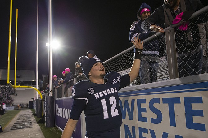 Nevada quarterback Carson Strong celebrates with fans after a 55-28 win against New Mexico State in Reno on Oct. 9, 2021. (AP Photo/Tom R. Smedes)