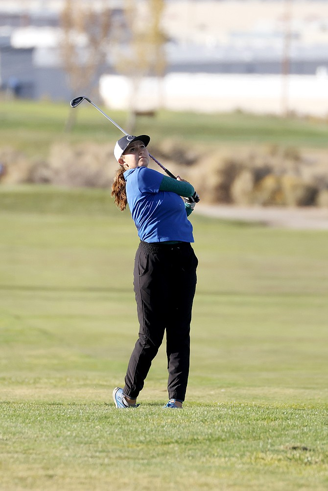 Carson High senior golfer Sarah Wiggins hits her approach shot on the 18th hole of the Sierra Sage Golf Course during the Class 5A regional tournament Wednesday. Wiggins was fourth as an individual after shooting a 78-83–161.