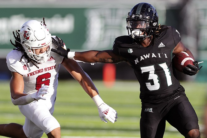 Hawaii running back Dedrick Parson stiff-arms Fresno State linebacker Levelle Bailey during their game Oct. 2, 2021, in Honolulu. (AP Photo/Marco Garcia)