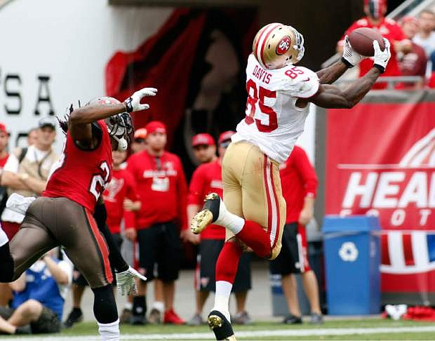 San Francisco 49ers tight end Vernon Davis (85) pulls in a 52-yard touchdown reception after getting past Tampa Bay Buccaneers strong safety Mark Barron (23) during the second quarter of an NFL football game Sunday, Dec. 15, 2013, in Tampa, Fla. (AP Photo/Reinhold Matay)