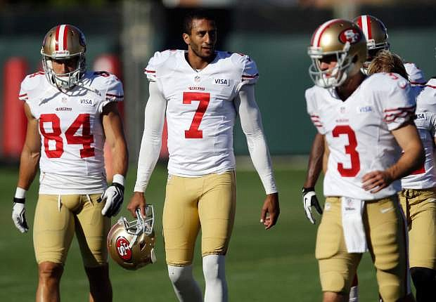 FILE - In this Aug. 2, 2013, file photo, San Francisco 49ers players, from left, Charly Martin, Colin Kaepernick, and Scott Tolzien walk on the field during NFL football training camp in Santa Clara, Calif. The man of few words, Kaepernick, has learned a thing or two from Peyton Manning. He just refuses to say what or offer any specifics. (AP Photo/Marcio Jose Sanchez, File)