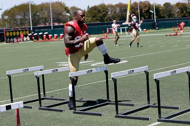 San Francisco 49ers tight end Vernon Davis jumps over hurdles during NFL football training camp on Thursday, July 25, 2013, in Santa Clara, Calif. (AP Photo/Marcio Jose Sanchez)