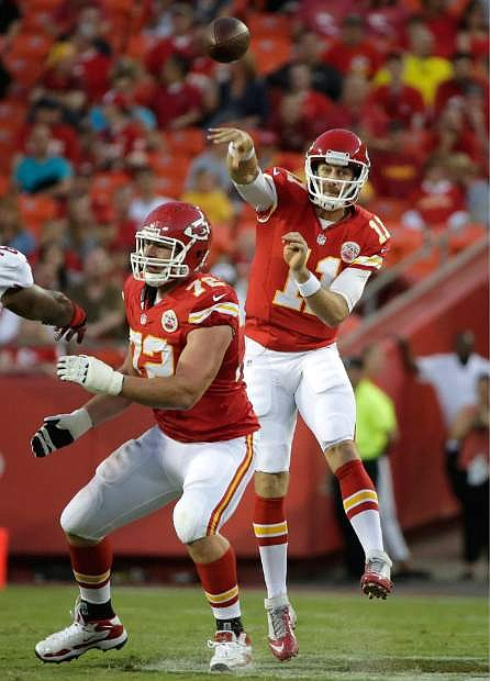 Kansas City Chiefs quarterback Alex Smith (11) passes behind the blocking of offensive tackle Eric Fisher (72) during the first half of an preseason NFL football game against the San Francisco 49ers at Arrowhead Stadium in Kansas City, Mo., Friday, Aug. 16, 2013. (AP Photo/Charlie Riedel)