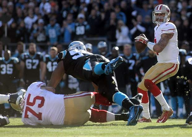 San Francisco 49ers Colin Kaepernick, right, looks to pass during a divisional playoff NFL football game against the Carolina Panthers, Sunday, Jan. 12, 2014, in Charlotte, N.C. (AP Photo/The Star, Ben Earp)