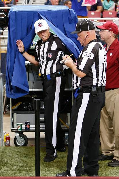 Referee Craig Wrolstad, left, leaves the instant replay monitor in the third quarter of an NFL football game between the St. Louis Rams and the San Francisco 49ers Monday, Oct. 13, 2014, in St Louis. At right is field judge Steve Zimmer (33). (AP Photo/Scott Kane)