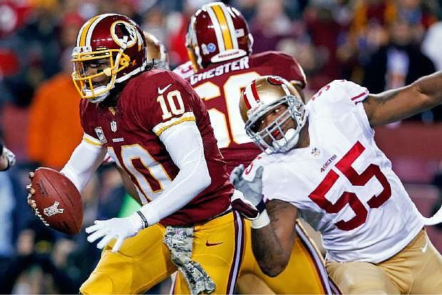 Washington Redskins quarterback Robert Griffin III scrambles away from San Francisco 49ers outside linebacker Ahmad Brooks during the first half of an NFL football game in Landover, Md., Monday, Nov. 25, 2013. (AP Photo/Alex Brandon)