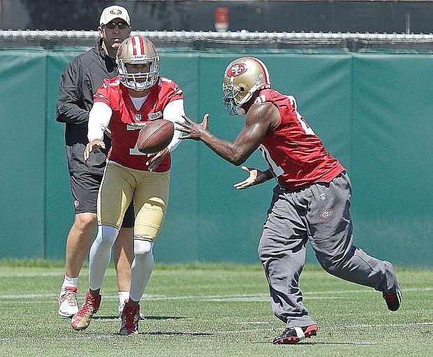 San Francisco 49ers quarterback Colin Kaepernick, front left, hands the ball off to running back Frank Gore during NFL football training camp on Friday, July 26, 2013, in Santa Clara, Calif. (AP Photo/Ben Margot)