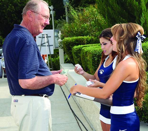 Tom Hall, former UNR Alumni President, purchases raffle tickets from cheerleaders Tristanne Gallardo and Hayley Canfield at the Governor's Dinner Friday.