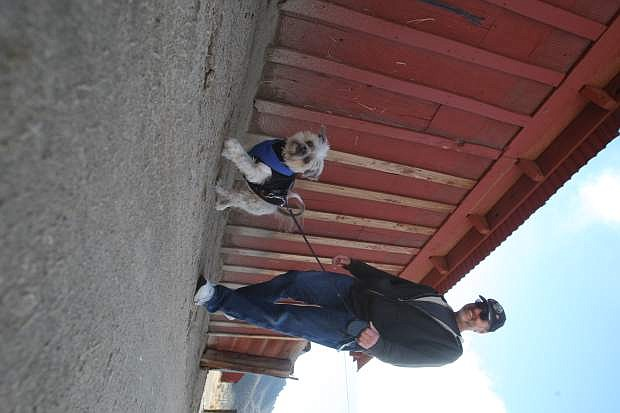 """Taking advantage of a warm afternoon, Carson City resident Louie Muratore walks """"Dusty"""" around the historic outback buildings of the Silver Saddle Ranch on Tuesday. The storm that hit during the weekend doubled the SIerra snowpack. See page A5 for more information. For a complete forecast, see page A19."""