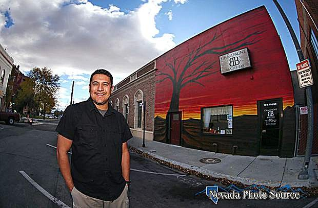 Artist Mauricio Sandoval poses with his Sunset Tree mural in downtown Carson City, Nev. on Tuesday, Oct. 25, 2016. The mural will officially be unveiled to the community during a ceremony 11:30 a.m. Friday.