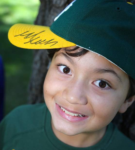 Colton Lokke, 10, is all smiles after former Oakland A's pitcher Mark Mulder autographed his ball cap on Tuesday at Edgewood.