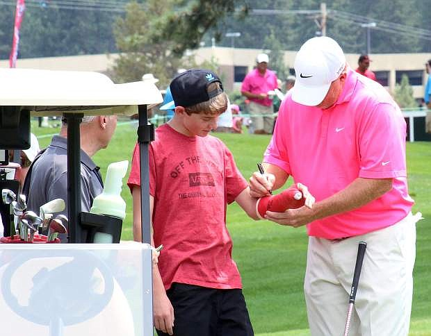 Former National Football League quarterback Billy Joe Tolliver signs an autograph during Wednesday's Lake Tahoe Celebrity-Am Tournament at Edgewood Tahoe Golf Course.