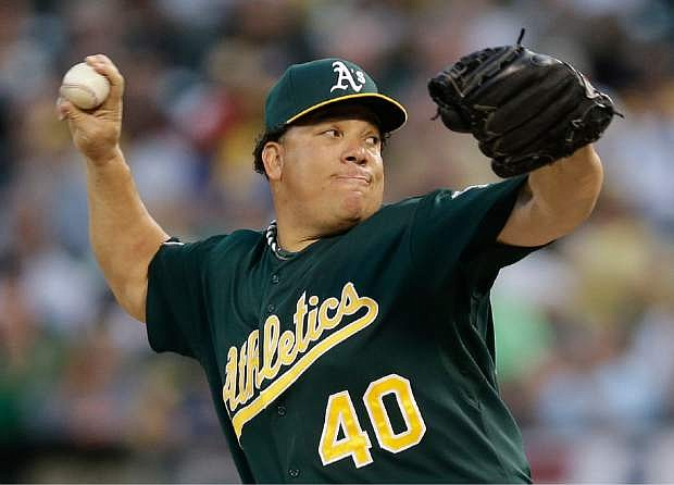 Oakland Athletics starter Bartolo Colon delivers a pitch in the first inning of Game 1 of the American League baseball division series against the Detroit Tigers in Oakland, Calif., Friday, Oct. 4, 2013. (AP Photo/Marcio Jose Sanchez)