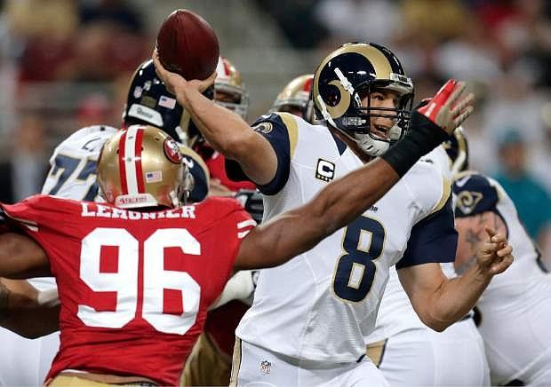 St. Louis Rams quarterback Sam Bradford (8) throws under pressure form San Francisco 49ers linebacker Corey Lemonier (96) during the first quarter of an NFL football game Thursday, Sept. 26, 2013, in St. Louis. (AP Photo/Charlie Riedel)
