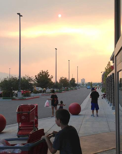 Smoke and haze from a wildfire more than 50 miles away darkens the sky over a shopping center parking lot in Sparks, Nev., late Sunday afternoon, Sept. 14, 2014. The wildfire, about 60 miles east of Sacramento, forced the evacuation of 133 homes. (AP Photo/Scott Sonner)