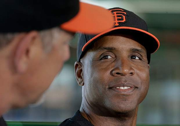 San Francisco Giants manager Bruce Bochy joins former player Barry Bonds at a news conference before a spring training baseball game in Scottsdale, Ariz., Monday, March 10, 2014. Bonds starts a seven day coaching stint today. (AP Photo/Chris Carlson)