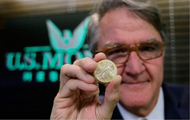 In this July 1, 2016, photo, Philip Diehl holds a 1-ounce gold coin at his office in Austin, Texas. Safety is a big draw since the shocking British vote to leave the European Union, sending gold prices soaring. (AP Photo/Eric Gay)