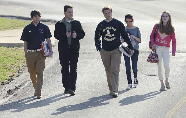 Students and a guardian walk to their car from Franklin Regional Middle School after more then a dozen students were stabbed by a knife wielding suspect at nearby Franklin Regional High School on Wednesday, April 9, 2014, in Murrysville, Pa., near Pittsburgh. The suspect, a male student, was taken into custody and is being questioned. (AP Photo/Tribune Review, Brian F. Henry)  PITTSBURGH OUT