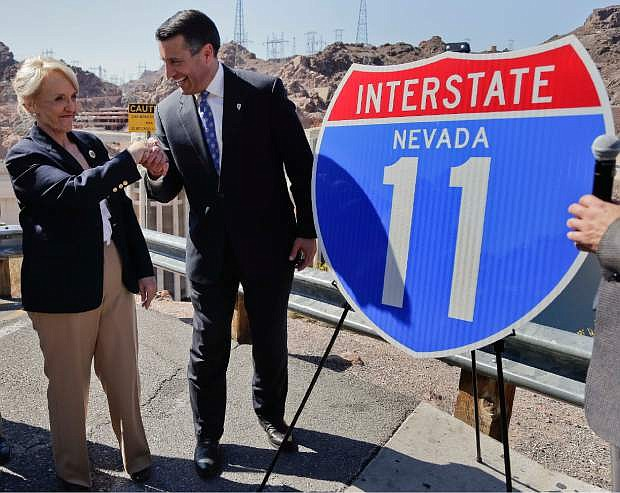 Arizona governor Jan Brewer, left, shakes hands with Nevada governor Brian Sandoval after unveiling a sign for the future Interstate 11, Friday, March 21, 2014, at Hoover Dam, Ariz.  The two governors gathered to unveil signs that will be posted along the proposed Interstate 11. It was a symbolic effort meant to keep up momentum on the project, which is coming of age in an era of scarce highway funding. (AP Photo/Julie Jacobson)