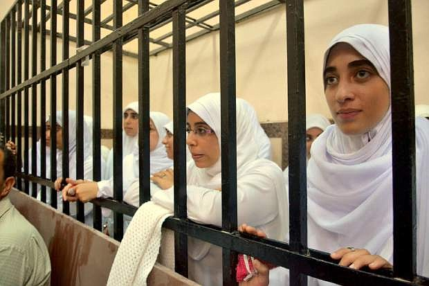 Egyptian women supporters of ousted President Mohammed Morsi stand inside the defentants' cage in a courtroom in Alexandria, Egypt, Wednesday, Nov. 27, 2013. An Egyptian court has handed down heavy sentences of 11 years in prison to 21 female supporters of the ousted Islamist president, many of them juveniles, for holding a protest. (AP Photo/Amira Mortada, El Shorouk Newspaper) EGYPT OUT