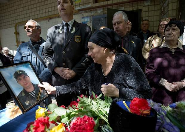 The mother of Dmitriy Nikityuk, a Cossack, holds holds his picture next to his coffin during the funeral in Odessa, Ukraine, Thursday, May 8, 2014. Nikityuk died of gas poisoning in the burning trade union building fire that killed most of the 40 people that died after riots erupted last Friday.(AP Photo/Vadim Ghirda)