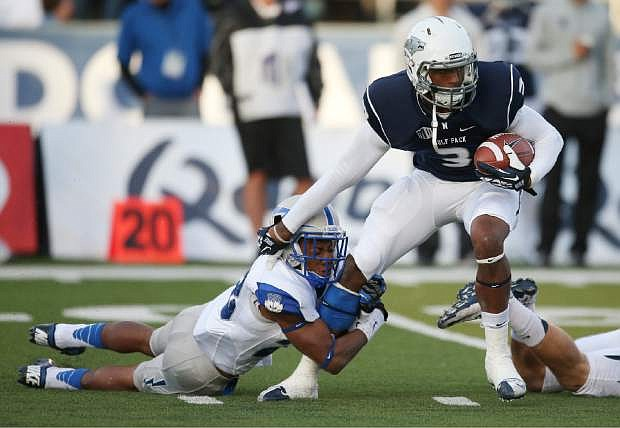 Nevada's Nigel Westbrooks (3) attempts to break a tackle from Air Force's Kalon Baker (28) during the first half of an NCAA college football game in Reno, Nev., on Saturday, Sept. 28, 2013. (AP Photo/Cathleen Allison)