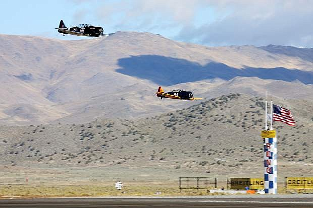 """A pair of T-6 class racers cross the finish line at home pylon in a 1 versus 1 single lap from a standing start """"drag race""""."""