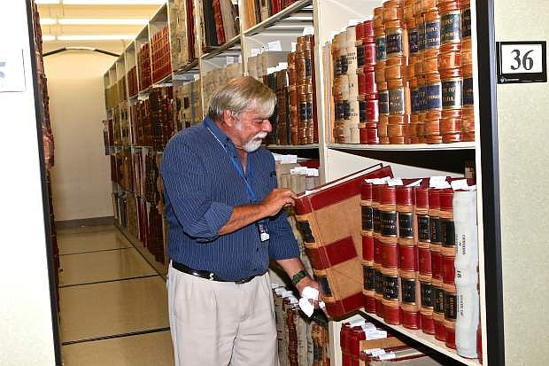 Nevada State Archivist Jeff Kintop pulls a giant book full of handwritten legislative notes from its slot in the basement of the archives Thursday morning in Carson City.