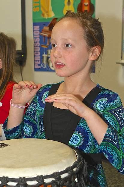 Braelynn Hudson, 7, plays a bongo drum during class Friday at Mark Twain Elementary.
