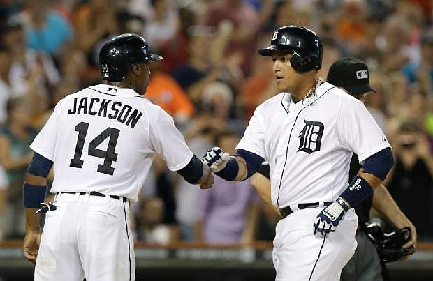 Detroit Tigers' Miguel Cabrera celebrates with Austin Jackson (14) after hitting a two-run home run against the Oakland Athletics in the fifth inning of a baseball game in Detroit, Monday, Aug. 26, 2013. (AP Photo/Paul Sancya)