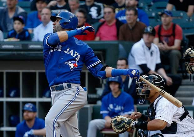 Toronto Blue Jays' Jose Bautista hits a two-run home run off Chicago White Sox starting pitcher Dylan Axelrod, also scoring Melky Cabrera, during the first inning of a baseball game Monday, June 10, 2013, in Chicago. (AP Photo/Charles Rex Arbogast)
