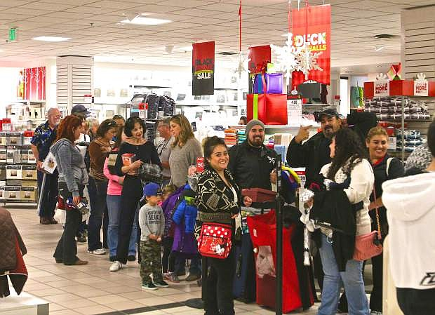 Customers at JCPenney wait in line to purchase their Black Friday items.